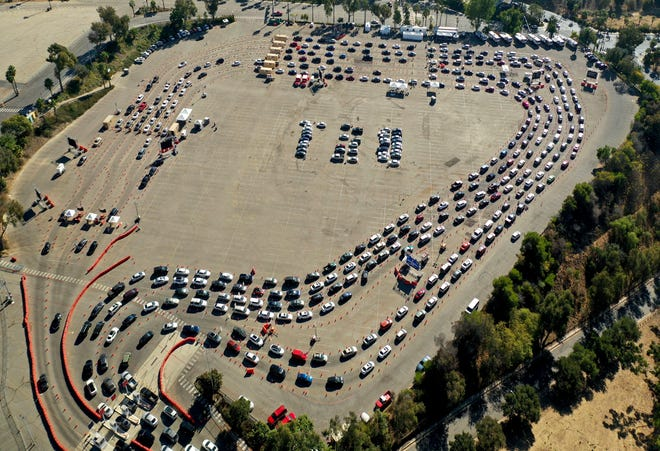 Drivers wait in long lines Nov. 17, 2020, at a COVID-19 testing site in a parking lot at Dodger Stadium in Los Angeles. The number of people hospitalized with COVID-19 in the U.S. has doubled in the past month and set new records every day this week.