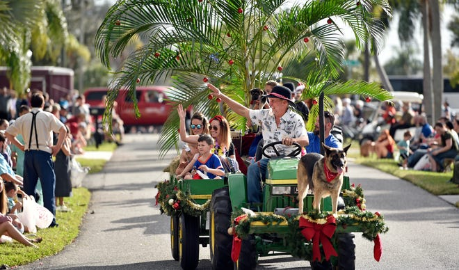 John Yoder, of Sarasota, with mascot Anna (out front) along with his family and friends ride along the route during Pinecraft's 24th annual Christmas Day Parade that had more than two thousand spectators lining the streets of Sarasota's Amish and Mennonite community on Christmas afternoon, Dec. 25, 2019. The parade is scheduled to return Friday. [HERALD-TRIBUNE STAFF PHOTO / THOMAS BENDER]