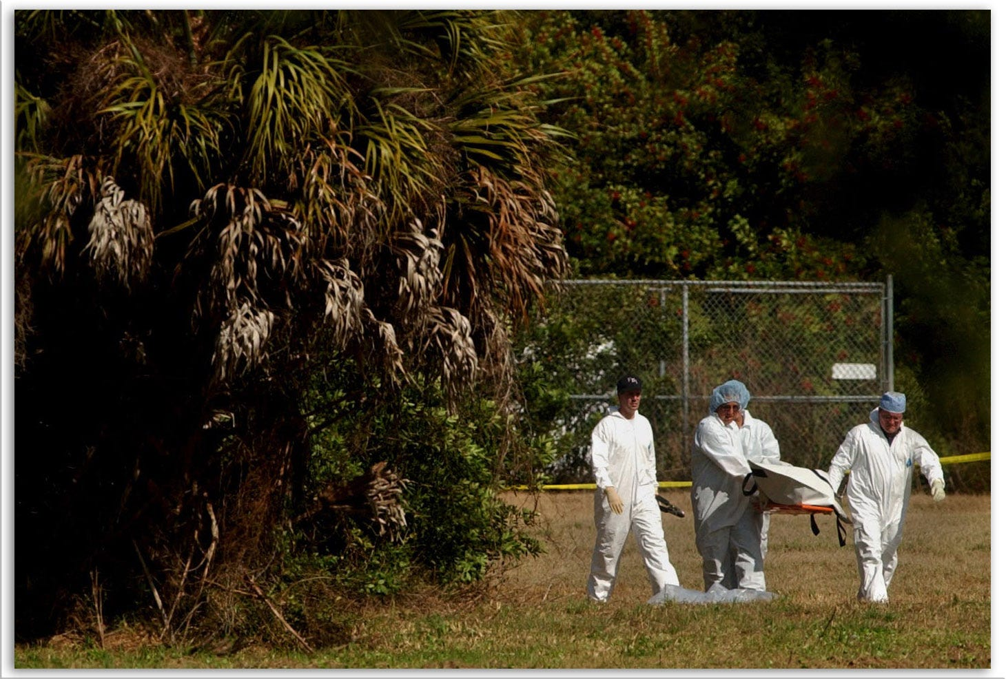 Investigators carry a body from the woods behind Central Church of Christ off Proctor Road in Sarasota, where 11-year-old Carlie Brucia was found dead Feb. 6, 2004.