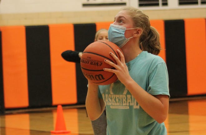 Kewanee High School sophomore Emma Crofton receives socially-distanced instruction from coach Jessica Shipley during a short-range shooting drill.