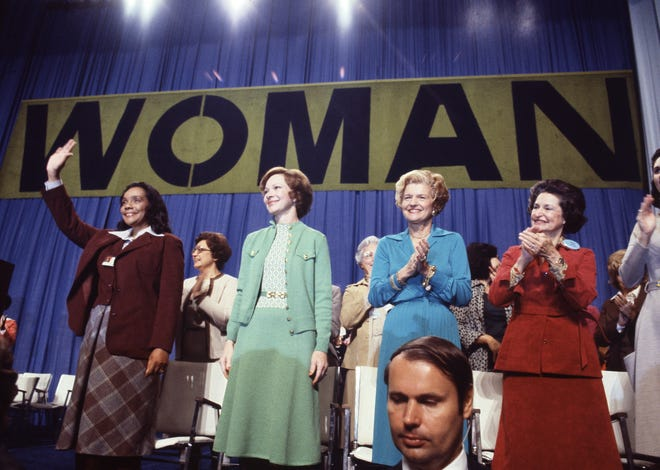 Coretta Scott King, widow of Dr. Martin Luther King Jr., waves as first ladies Rosalynn Carter, Betty Ford and Lady Bird Johnson applaud at the National Women's Conference in Houston, Texas, Nov. 19, 1977.