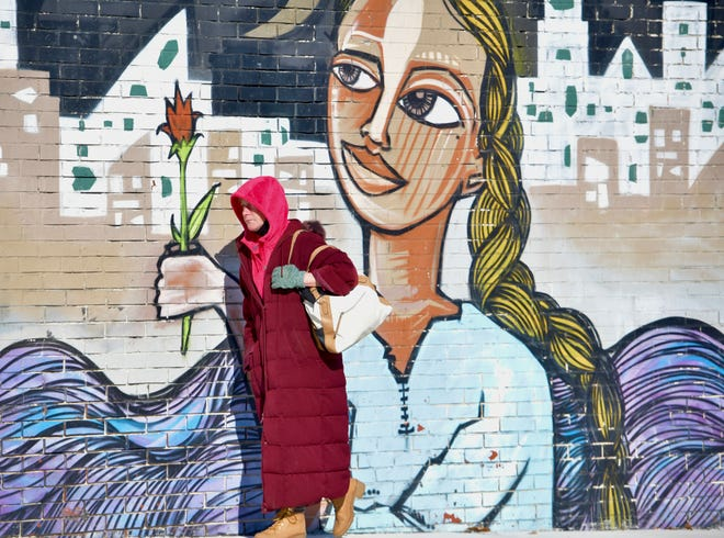 """WORCESTER - A woman bundled up against the cold walks past the Alice Mizrachi mural """"Maiden Mother Crone"""" on Francis J. McGrath Boulevard near Green Street on Wednesday morning."""