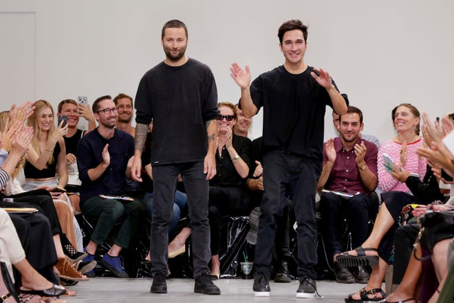 Designers Jack McCollough, left, and Lazaro Hernandez, of Proenza Schouler acknowledge audience applause after their Spring 2017 collection was modeled during Fashion Week in New York on Sept. 12, 2016. The designer duo have been thinking about longterm changes to the way they and their colleagues work. In an interview they mused that maybe less is more and they don't need to do runway shows with every collection.