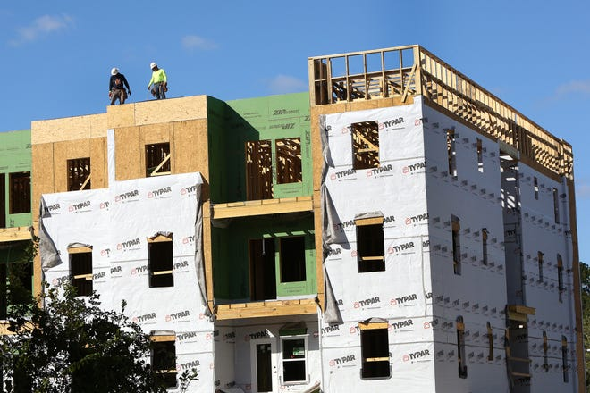 A construction crew works to build a new apartment complex off Southwest 13th Street in Gainesville on Nov. 18.