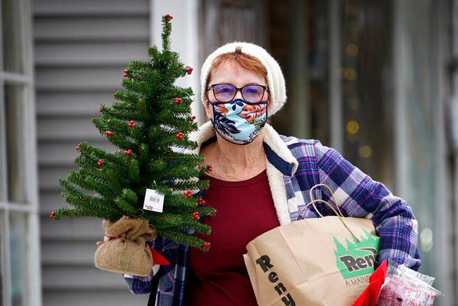 A woman wears a face covering to help prevent the spread of the coronavirus after shopping for holiday decorations Nov. 13 in Bridgton, Maine.