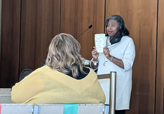 "Diann Cylar holds up a copy of Bryan Stevenson's book ""Just Mercy"" during a Human Relations Advisory Committee meeting on Tuesday, Nov. 17, 2020."