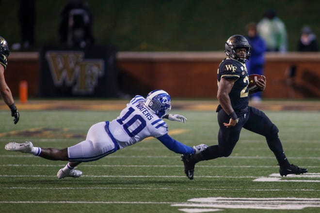 Wake Forest running back Kenneth Walker III, right, avoids Duke safety Marquis Waters in a game last season. This Saturday's scheduled matchup between the two teams has been called off due to COVID-19 cases within the Demon Deacons program.