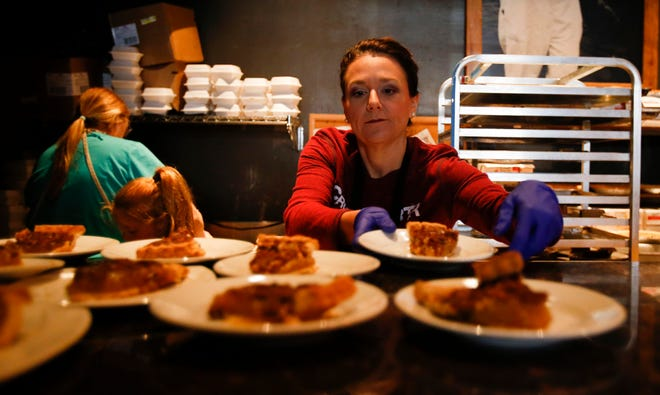 Rosann Turner sets plates of pecan pie on the counter as orders come in at the 8th annual Thanksgiving Feast benefiting Habitat for Humanity held at Chuck's Fish in downtown Tuscaloosa on Thursday, Nov. 23, 2017.   [Staff Photo/Erin Nelson]