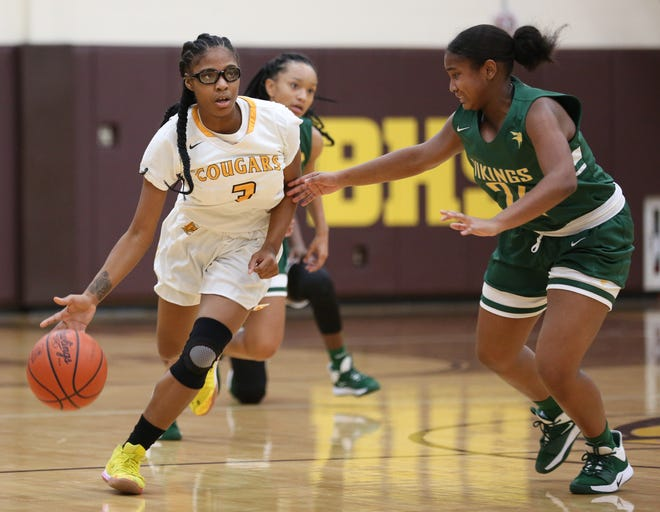 Beechcroft's LaBriar Franklin-Page drives to the basket against Northland's Ayah Duffy during a game last season. Both are key returnees this winter. The Cougars are hoping to unseat the Vikings as champions of the City League-North Division.