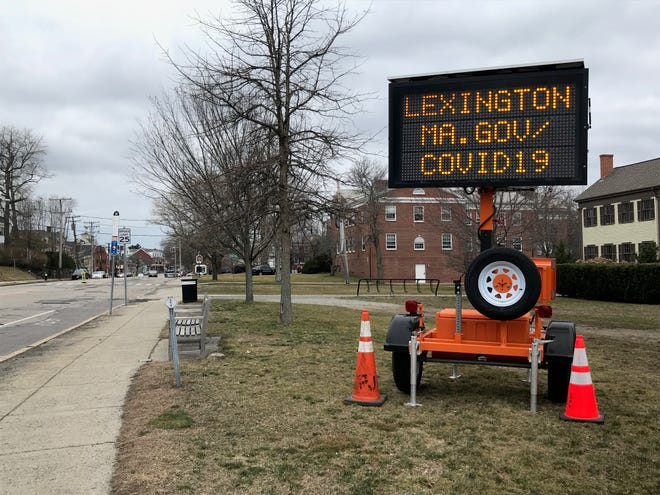 A sign along Massachusetts Avenue directs Lexington residents to the town's website for more information on the pandemic.