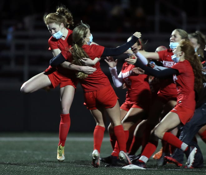 Hingham's Claire Murray jumps in the arm of Sophie Reale after she scored the game winning penalty kick to give Hingham the 4-2 advantage over Whitman-Hanson during their semifinal game in the Patriot Cup at Hingham High on Tuesday, Nov. 17, 2020.