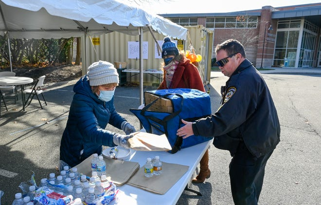 Dottie Kitoski and Swampscott Police Sargent Matthew MacDonald work together to package slices of pizza to be handed out to seniors along with a COVID Care Package during a drive-thru event outside the Swampscott Senior Center on Wednesday, Nov. 18, 2020.