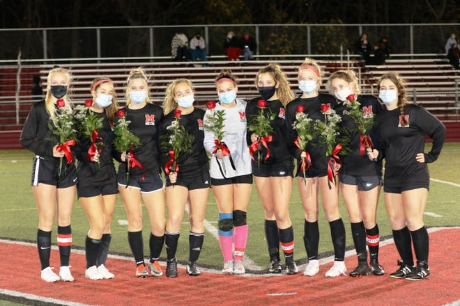 Marblehead girls' soccer seniors Josie Poulin, Samantha McKay, Natalie Paquette, Leah Saulnier, Lauren Podger, Elizabeth Driscoll, Leila Walton, Anna Rigby and Mae Genovese, from left, are shown being honored for their contributions to the program the last four years on Senior Night last Friday night, Nov. 13, before the game against Salem. [Courtesy photo / Muffy Paquette]