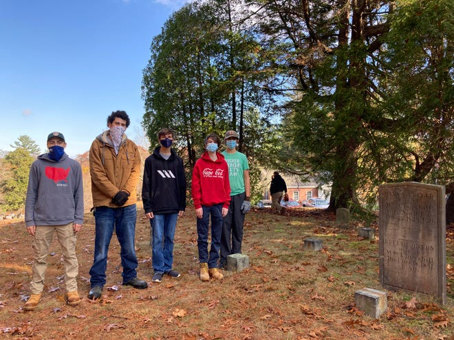 Scout Tristan Holmes with help from Clayton Marshall, Nick Bartlett, Chris Bartlett and Jack George work to clear a portion of the Old Burying Ground in Kingston.
