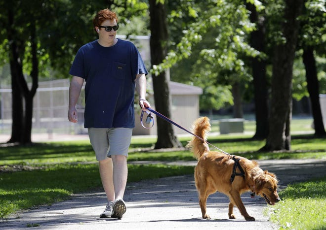 Michael Seveska of Neenah and his dog, Wrigley, walk through Southview Park in Neenah earlier this year. The city is working to develop an off-leash dog park at 350 Byrd Ave.