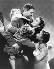 """Karolyn Grimes, top left, with Jimmy Stewart, Donna Reed and the cast of Frank Capra's """"It's a Wonderful Life."""""""