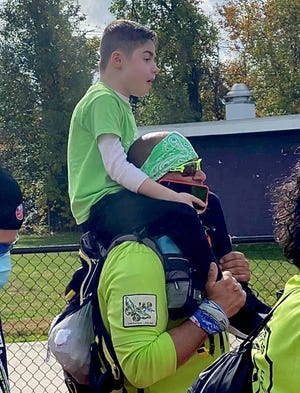 Jamesy Raffone riding atop dad Jim Raffone's shoulders during a JAR of Hope event