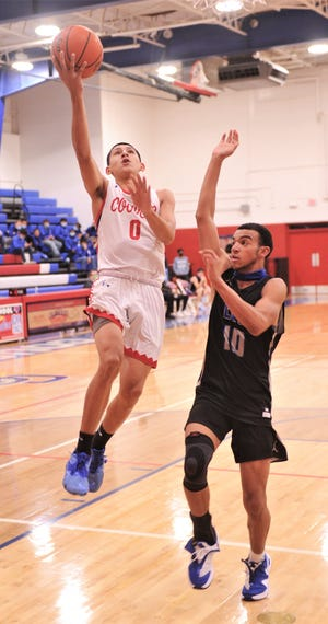 Cooper's Darrien Villarreal (0) drives to the basket as San Angelo Lake View's Deshawn Powell. Cooper beat the Chiefs 72-25 in the nondistrict game Tuesday at Cougar Gym.