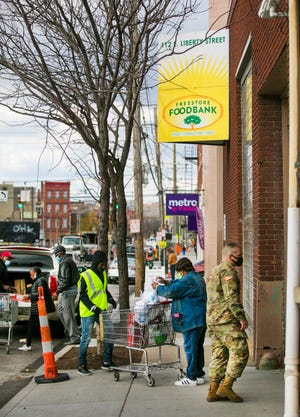 Volunteers, along with the National Guard, help Freestore Foodbank clients load their groceries in Over-The-Rhine last month.