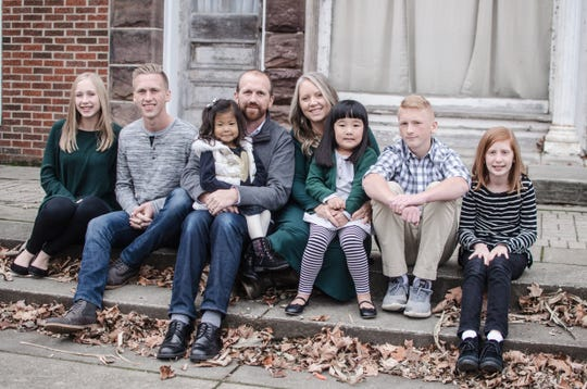 The Sommers family poses for a photo in Canal Fulton a few weeks before Olive's surgery. They are (L to R) Taylor, Landon, Olive on her dad, Paul's lap, Angie, Josie, Kyle and Adison.
