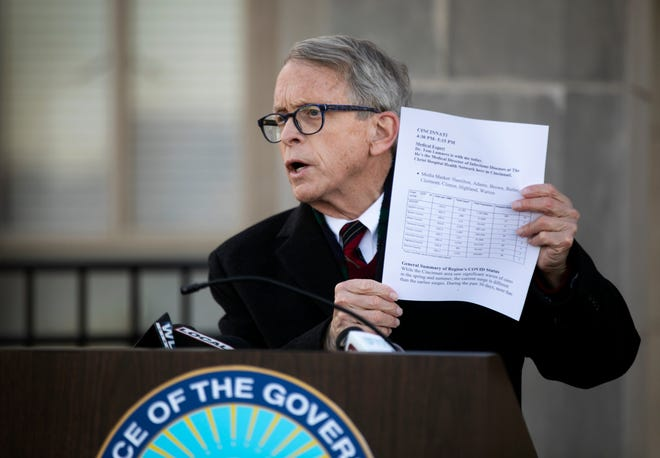 Gov. Mike DeWine shows COVID-19 numbers for the Cincinnati area during a press conference at Lunken Airport, Wednesday, Nov. 18, 2020. DeWine traveled across the state to enforce the curfew and the importance of masks and social distancing during the coronavirus pandemic.