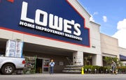 In this March 22, 2020 file photo, customers wearing masks walk into a Lowe's home improvement store in the Canoga Park section of Los Angeles.
