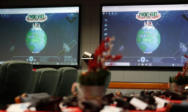 Monitors are illuminated in the NORAD Tracks Santa center at Peterson Air Force Base in Colorado Springs in this Dec. 23, 2019, file photo. The North American Aerospace Defense Command has announced that NORAD will track Santa this year, just as it has done for 65 years. But there will be some changes.