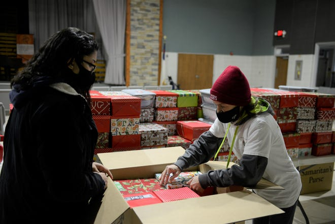 Leandra Viscioni, left, and Diane Hardin pack boxes with gifts Wednesday morning at Freedom Ridge Church for the Samaritan's Purse Operation Christmas Child.