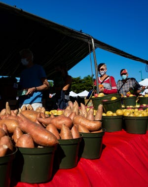 Customers line up to purchase fresh produce at Aurora Fresh Produce at the Marco Island Farmers' Market.