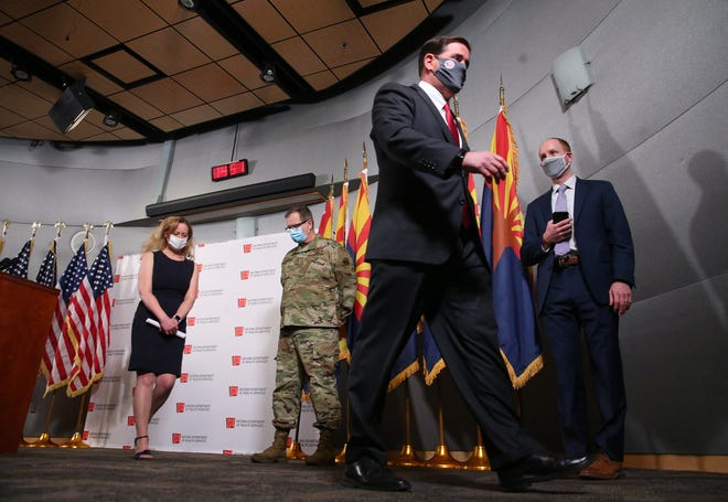 Arizona Gov. Doug Ducey walks out after addressing the media about COVID-19 during a news conference in Phoenix on Nov. 18, 2020.