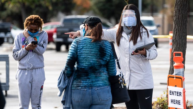 Esmeralda Zamora assists those seeking a COVID-19 test during Tulare County Health Department's free flu vaccination and COVID-19 testing clinic in the John Muir parking lot of College of the Sequoias on Wednesday, November 18, 2020. Zamora is a public health inspector for the County.