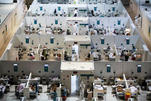 Medical workers and patients are seen in the treatment hall of a temporary hospital for coronavirus patients in the Krylatskoye Ice Palace in Moscow, Russia, Wednesday, Nov. 18, 2020. The resurgence of the outbreak has swept the Russia since September, with the number of daily new cases spiking from roughly 5,000 in early September to over 22,000 this week.