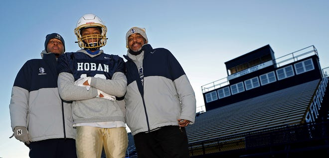 Hoban receiver Shawn Parnell poses at Dowed Field with his father Renzy, defensive coordinator for the Knights, and his grandfather Renny, a defensive assistant for the team, Wednesday, Nov. 18, 2020, in Akron, Ohio. [Jeff Lange/Beacon Journal]