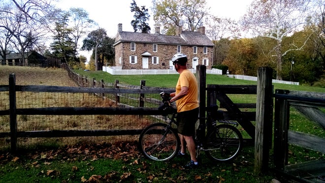 Biker Frank Williams pauses outside the Thompson-Neely House, once the site of an important Indian town known as Winnahawchunick, in today's upper section of Washington Crossing Historic Park in Solebury.