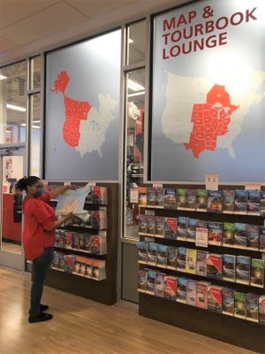 At the AAA Langhorne Car Care Insurance Travel Center in Oxford Valley Plaza, Middletown, travel agent Sharon Leitch checks out the store's wall of maps available to members who are planning trips. AAA will devise a Trip Tik with directions for its members.