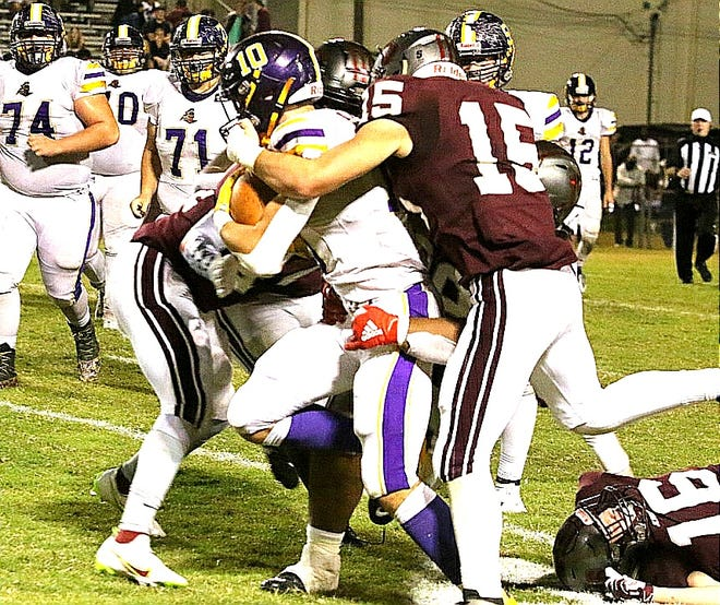 Nick Uhlik (10) fights off a facemask by a Jennings defender to pick up some extra yards in a 42-14 loss last week. Uhlik and the Golden Knights face Lake Charles College Prep on Saturday.