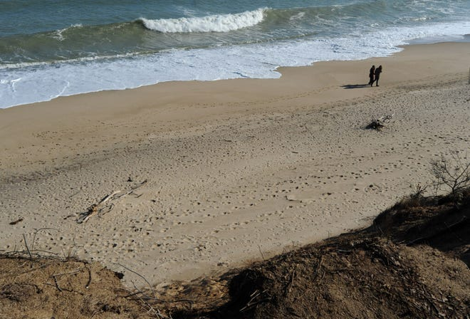 NORTH EASTHAM -- The outgoing tide crashes over the sandbar off Nauset Light Beach seen from the top of the erosion eaten cliffs.