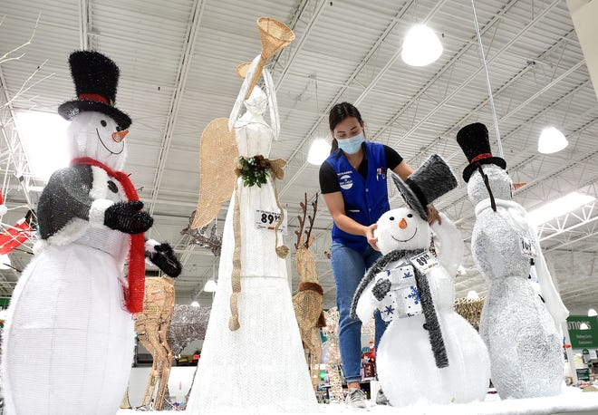 Macey Link, a sales team associate at Menards, assembles a Christmas display in preparation for Black Friday.