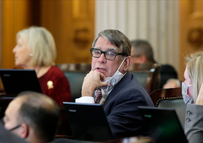 Ohio House of Representatives Majority Floor Leader Bill Seitz (Rep.) lowers his mask while speaking to a colleague during a session at the Ohio Statehouse on Wednesday, November 18, 2020.