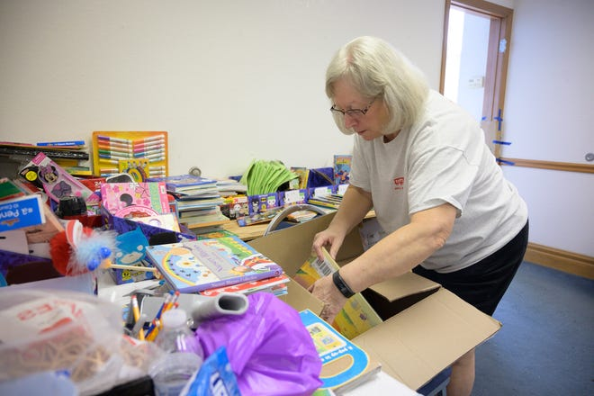 A volunteer packs stocking stuffers for kids at the Toys for Tots distribution facility in Fruitland Park on Thursday, Dec. 12, 2019.
