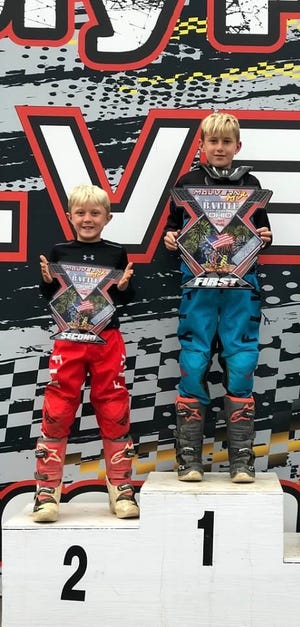 Racing brothers nine-year-old Cash, right, and seven-year-old Coy Jackson, left, of Barnesville, are shown on the championship podium following an ATV race last season.