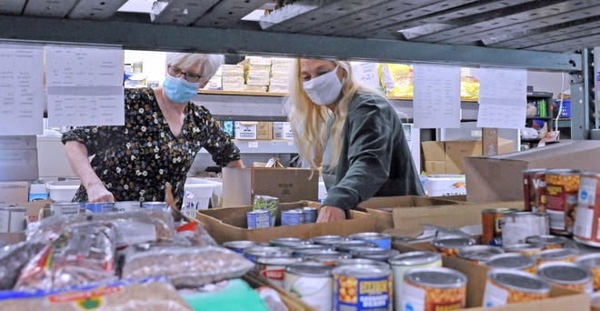 Theresa Markley and Vicky Petty pack a box food for a Thanksgiving dinner. People to People Ministries has provided help to the community even throughout the coronavirus pandemic.