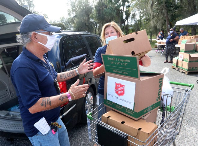 Chaplain Victor Muniz and Lynn Sutton load turkeys and all the fixings for a Thanksgiving dinner, Thursday November 19, 2020, into a waiting motorist's vehicle. Volunteers had 500 meals to give away at the Salvation Army in DeLand.