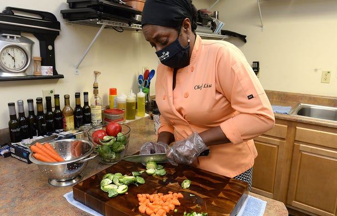 Lisa Heidelberg, owner of Dinner is Served by Lisa, prepares roasted Brussels sprouts recently at her Erie business. Heidelberg offers ready-to-go meals weekly and will be offering catered Christmas Day family meals.