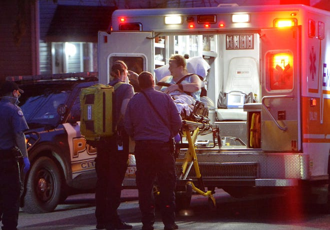 A female stabbing victim, center, is helped into an EmergyCare ambulance in the 200 block of East Fourth Street on Thursday in Erie.