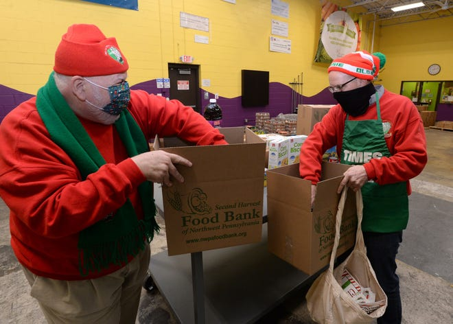 Old Newsies Lewis Nordin Sr., left, sale day chairman, and Scott Barnes, president, fill a holiday food box Nov. 19 at the Second Harvest Food Bank of Northwest Pennsylvania.