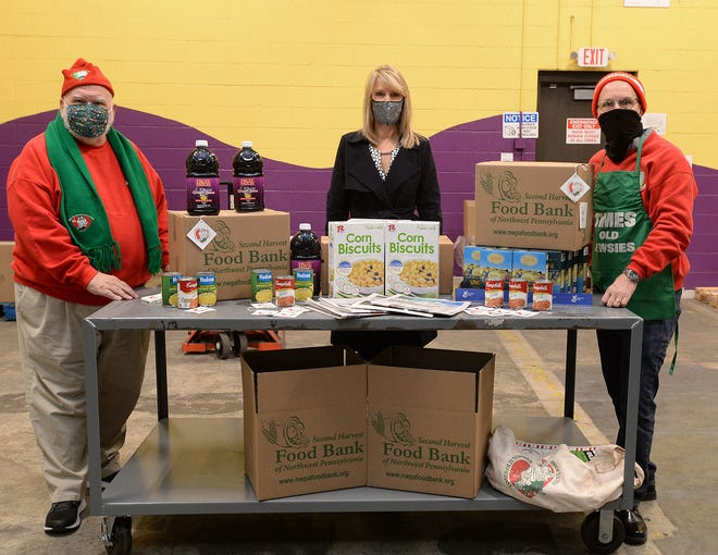 Lewis Nordin Sr., left, Old Newsies sale day chairman; Karen Seggi, center, chief executive officer of the Second Harvest Food Bank of Northwest Pennsylvania; and Scott Barnes, right, Old Newsies president, are shown Nov. 19 at the Second Harvest Food Bank of Northwest Pennsylvania.