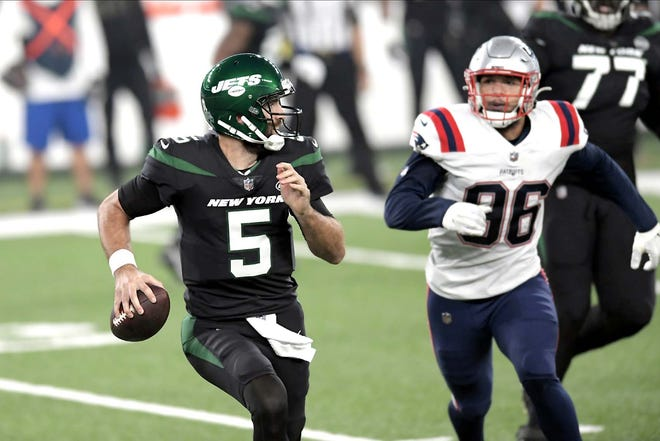 New York Jets quarterback Joe Flacco (left) looks to throw against the New England Patriots during a Nov. 9 game in East Rutherford, New Jersey.