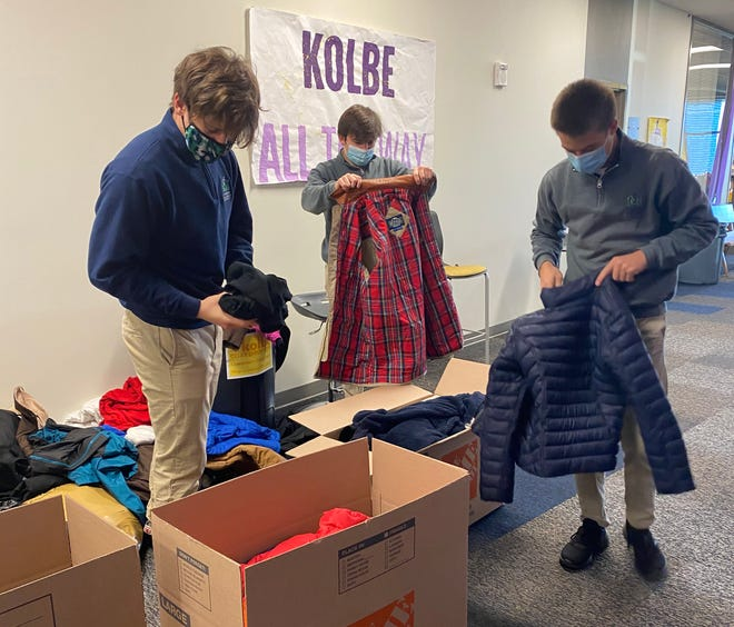 St. Michael the Archangel senior, Jacob Smitka, left to right, and friends Cooper Garlick and John Samson begin packing some of the 296 coats that were collected in Smitka's Coats for a Cause charity drive at the Lee's Summit high school.