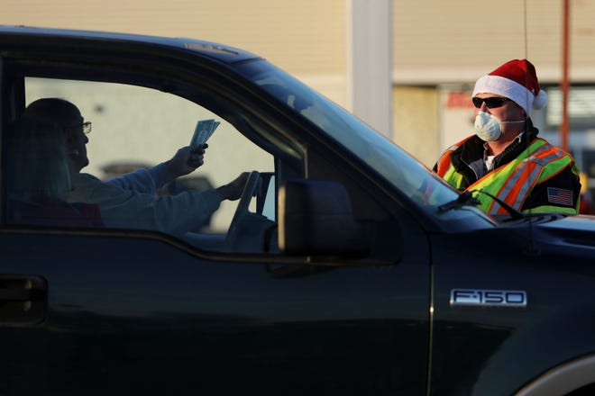 """West Burlington firefighter Travis Sours collects donations for the department's first-ever """"Fill the Stocking for the Kids!"""" Wednesday near the intersection of Broadway and Agency streets in West Burlington."""